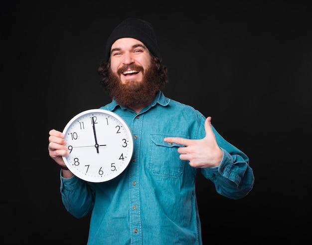 Homem barbudo bonito e alegre apontando para um grande relógio branco