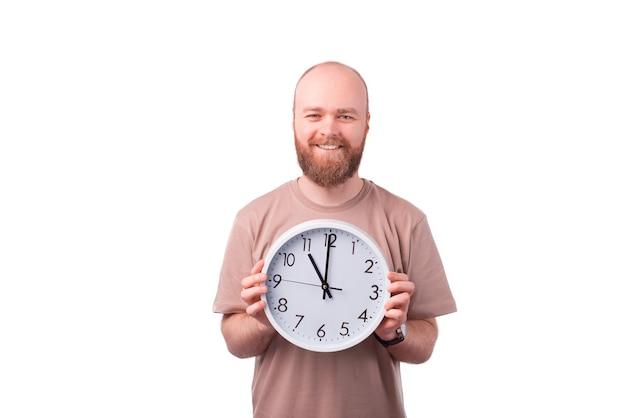 Homem barbudo bonito e alegre segurando um relógio branco