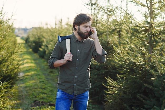 Homem barbudo bonito e positivo com machado que caminha entre as fileiras de árvores de natal na silvicultura e