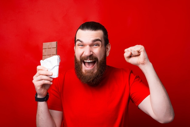 Homem barbudo bonito e surpreso segurando chocolate e gesticulando, o melhor chocolate