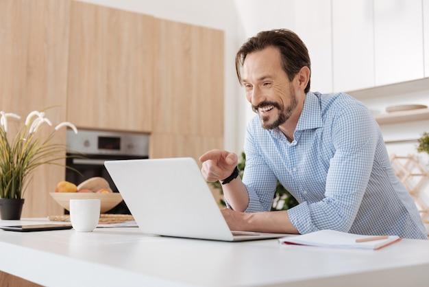 Homem barbudo bonito em pé atrás do balcão da cozinha, olhando para o laptop e apontando para ele com o dedo enquanto ri.