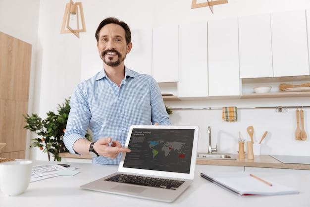 Homem barbudo bonito em pé atrás do balcão e apontando com o dedo para o laptop, virado para o público.