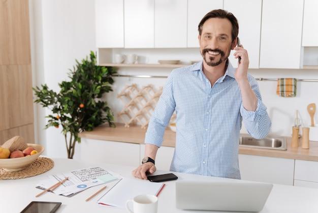 Homem barbudo bonito em pé na cozinha atrás do balcão da cozinha, falando ao telefone e sorrindo para a câmera.