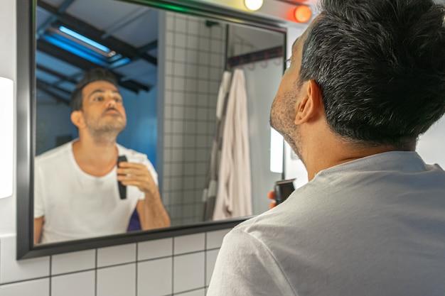 Homem barbudo bonito está barbeando o rosto e o pescoço com uma máquina de cortar na frente do espelho do banheiro.