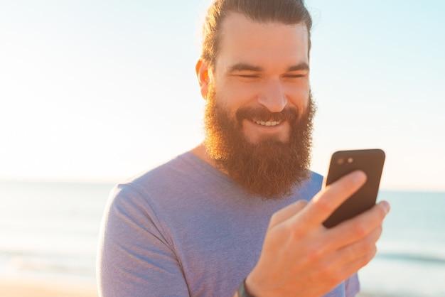 Homem barbudo bonito está enviando mensagens de texto ou navegando em seu telefone ao ar livre.