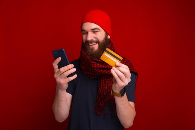 Homem barbudo bonito está sorrindo e comprando natal on-line perto de parede vermelha.