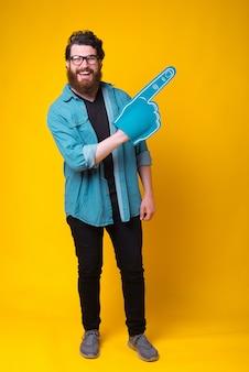 Homem barbudo bonito está usando uma luva de espuma de ventilador em pé