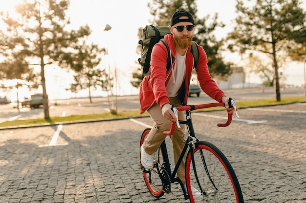 Homem barbudo bonito estilo hippie com capuz vermelho e óculos de sol andando sozinho com mochila em bicicleta mochileiro viajante estilo de vida ativo saudável