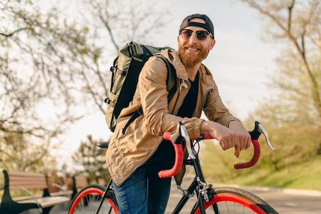 Homem barbudo bonito estilo hippie com jaqueta e óculos escuros andando sozinho com a mochila na bicicleta mochileiro viajante estilo de vida ativo saudável