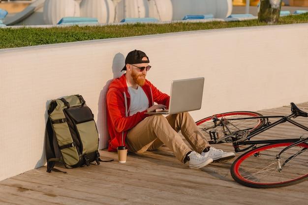 Homem barbudo bonito estilo hippie trabalhando online freelancer no laptop com mochila e bicicleta no nascer do sol da manhã à beira-mar estilo de vida ativo saudável mochileiro viajante