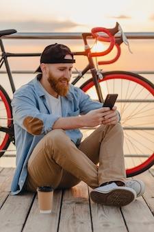 Homem barbudo bonito estilo hipster vestindo camisa jeans e boné segurando smartphone com bicicleta no nascer do sol da manhã à beira-mar bebendo café, viajante saudável estilo de vida ativo