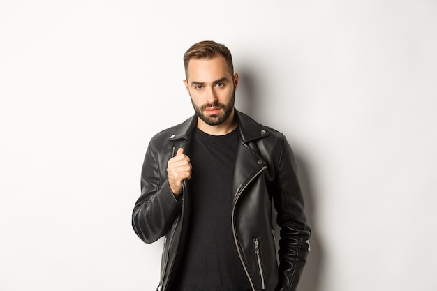 Homem barbudo bonito expressando confiança, tocando sua jaqueta de couro e parecendo autoconfiante