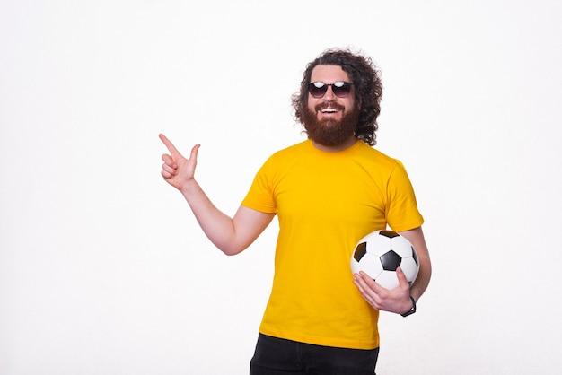 Homem barbudo bonito feliz segurando uma bola de futebol e apontando para longe