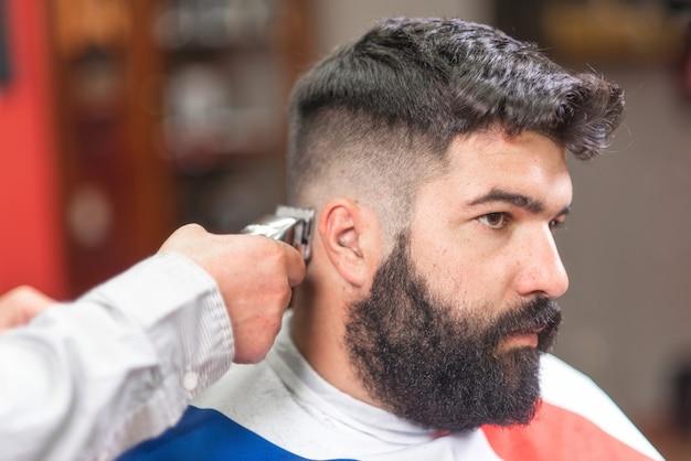 Homem barbudo bonito, ficando o corte de cabelo pelo barbeiro