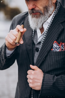 Homem barbudo bonito fumando cigarro Foto gratuita