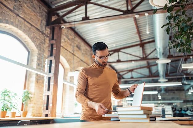Homem barbudo bonito. homem barbudo bonito olhando para os livros enquanto trabalhava em uma editora