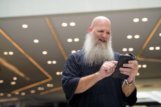 Homem barbudo bonito maduro e feliz usando o telefone na cidade ao ar livre