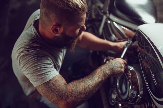 Homem barbudo bonito na jaqueta de couro e óculos de sol está sentado na motocicleta na oficina