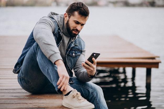 Homem barbudo bonito pelo rio no parque, sentado na doca