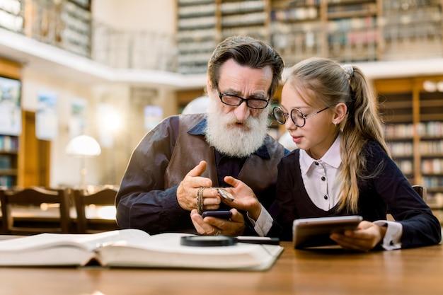 Homem barbudo bonito sênior e sua neta bonita olhando um relógio vintage em uma cadeia, enquanto está sentado à mesa com livros, tablet e telefone na biblioteca antiga.