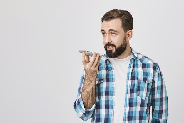 Homem barbudo bonito sério grava mensagem de voz com viva-voz