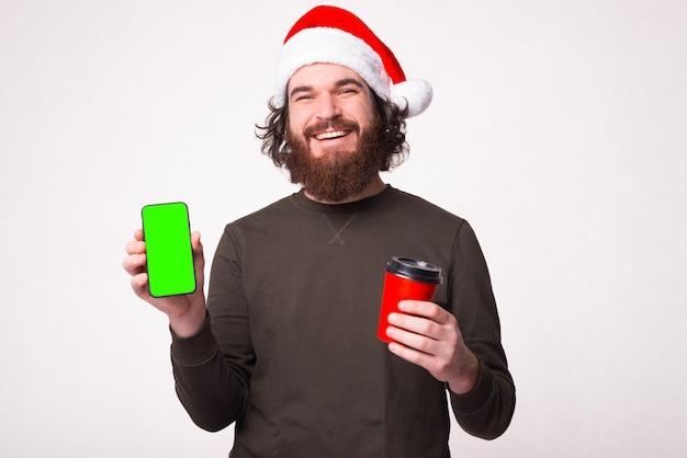 Homem barbudo bonito sorrindo e mostrando o telefone com tela verde e segurando uma xícara de café para ir