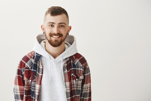 Homem barbudo bonito sorrindo feliz e olhando para frente