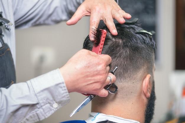 Homem barbudo bonito, tendo o cabelo cortado por uma tesoura na barbearia.
