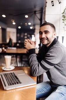 Homem barbudo bonito tomando café enquanto trabalhava em um café