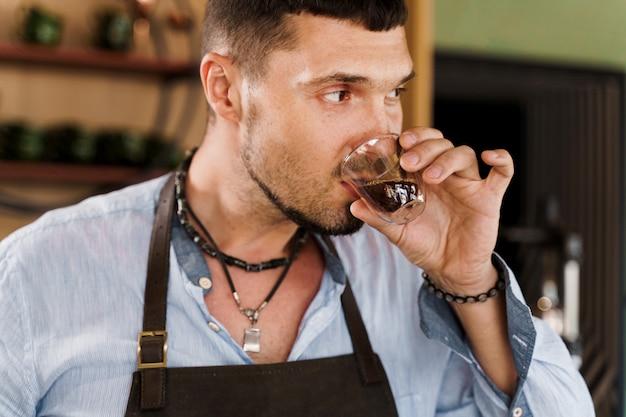 Homem barbudo bonito tomando café expresso em copo de vidro duplo
