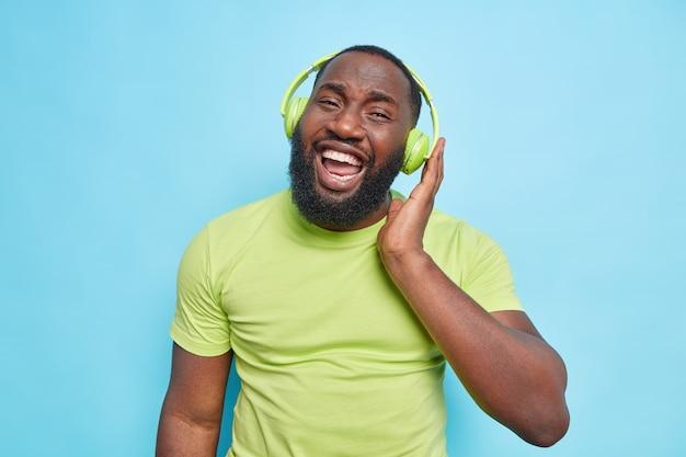 Homem barbudo bonito usa fones de ouvido verdes e camiseta gosta de ouvir sorrisos de música amplamente isolados sobre a parede azul