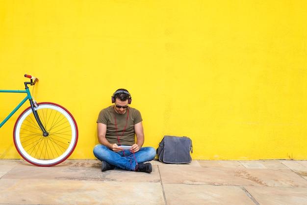 Homem barbudo bonito usando um telefone celular enquanto ouve música em fones de ouvido, gastando tempo com prazer enquanto está sentado perto da bicicleta, ao ar livre
