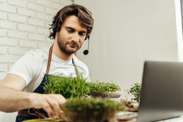 Homem barbudo bonito vende brotos de plantas e mudas on-line usando um laptop por videochamada