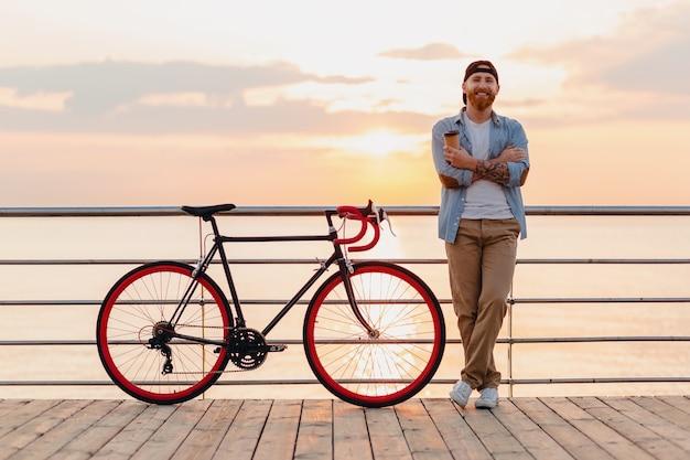 Homem barbudo bonito viajando de bicicleta no nascer do sol da manhã à beira-mar, bebendo café, viajante saudável, estilo de vida ativo