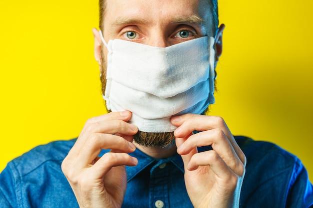 Homem barbudo branco coloca uma máscara no rosto contra a poluição do ar e o coronavírus covid-19.