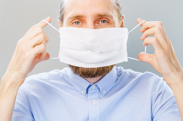Homem barbudo branco de camisa azul coloca uma máscara de poluição do ar e coronavírus covid-19.