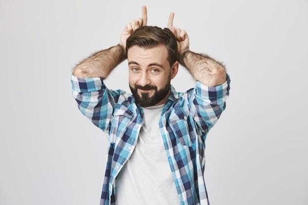 Homem barbudo brincalhão e engraçado fazendo gesto de chifres