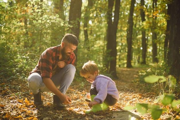 Homem barbudo brutal e menino desfrutam da natureza do outono. valores de família. explore a natureza. conceito de wanderlust. pai barbudo hipster com filho bonito passam um tempo juntos na floresta. tempo para a família. lazer em familia