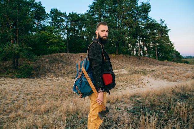 Homem barbudo brutal hipster de retrato na floresta com machado