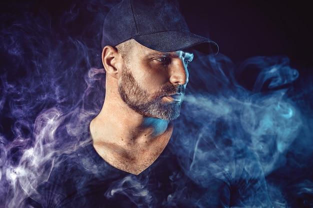 Homem barbudo brutal vaping e libera uma nuvem de vapor