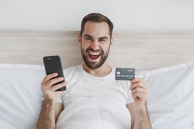Homem barbudo calmo deitado na cama com lençol branco e cobertor no quarto em casa