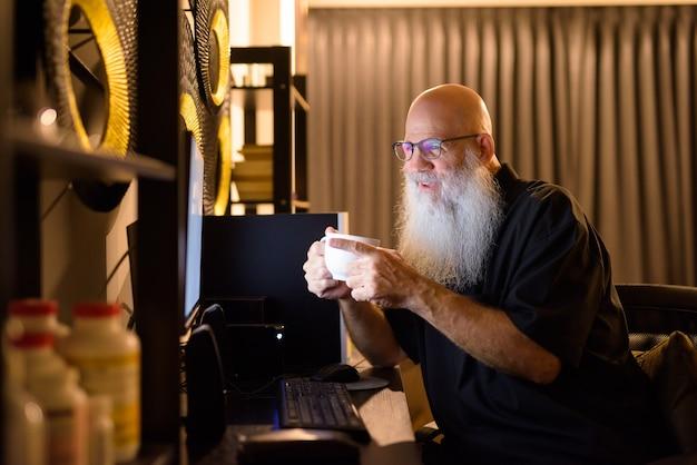Homem barbudo careca maduro e feliz bebendo café enquanto faz uma videochamada no trabalho de casa tarde da noite