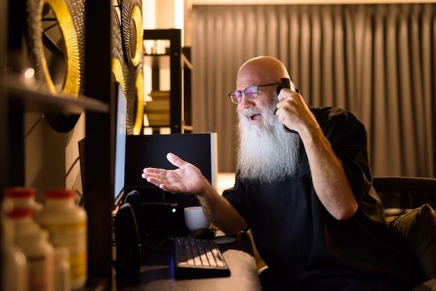 Homem barbudo careca maduro e feliz falando ao telefone enquanto trabalhava horas extras em casa tarde da noite