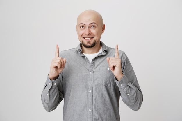 Homem barbudo careca sorridente apontando e olhando para cima