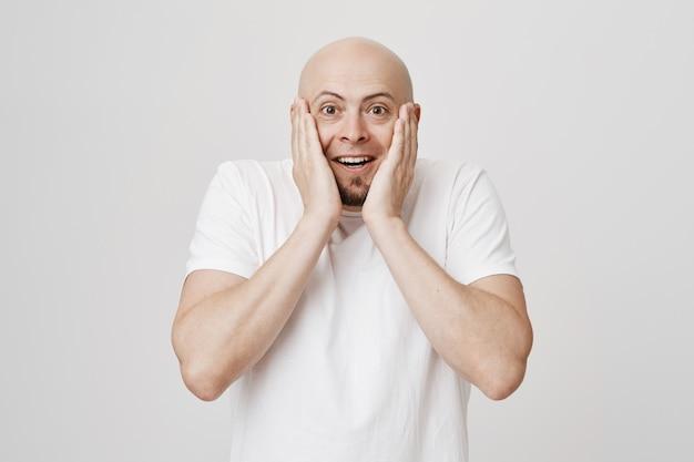 Homem barbudo careca surpreso e feliz tocando as bochechas e sorrindo maravilhado