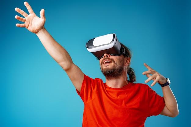 Homem barbudo casual usando óculos de realidade virtual