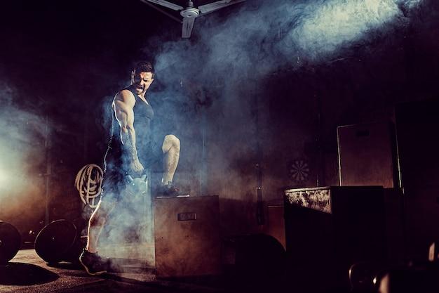 Homem barbudo caucasiano atraente muscular levantando dois kettlebells em um ginásio. placas de peso, halteres e pneus em segundo plano.