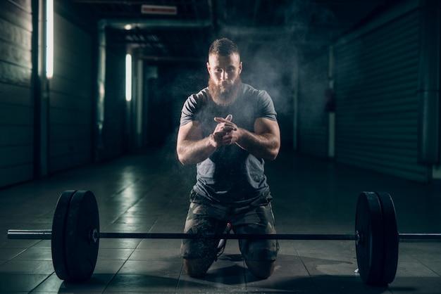 Homem barbudo caucasiano atraente muscular no corredor ajoelhado