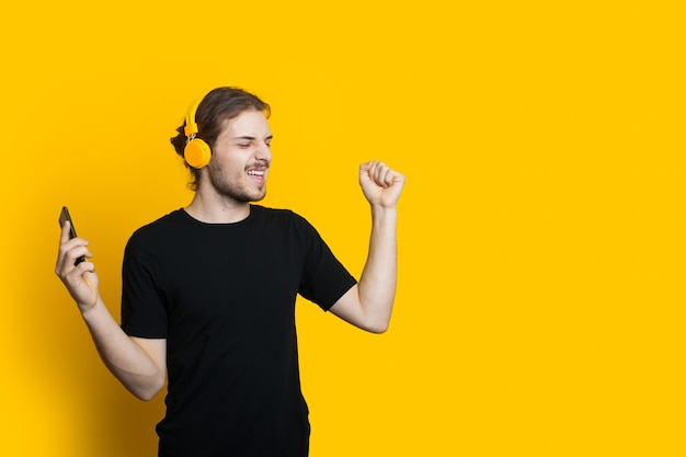Homem barbudo caucasiano com fones de ouvido e cabelo comprido dançando em uma parede amarela com espaço em branco