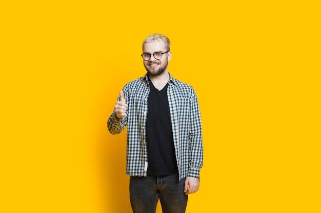 Homem barbudo caucasiano com óculos e cabelo loiro gesticulando o sinal de aprovação em uma parede amarela